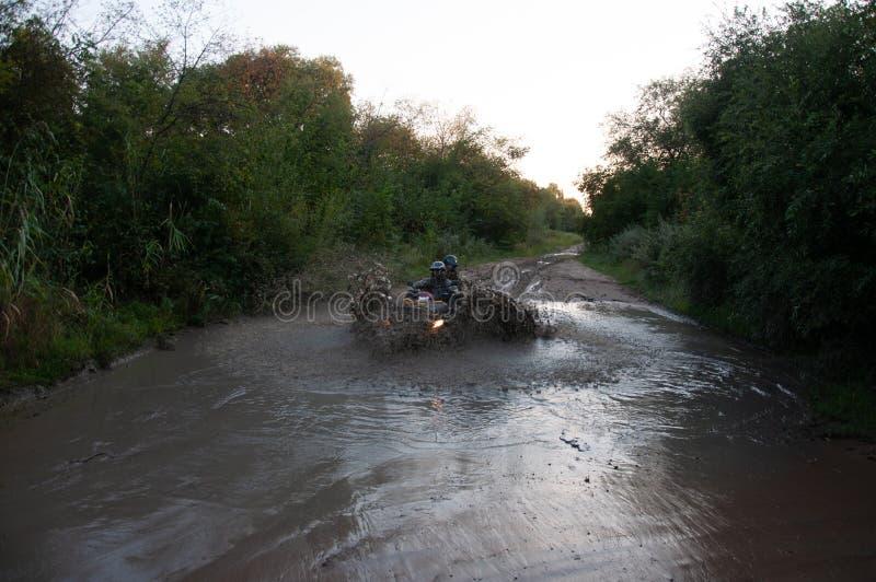 Il Quad ATV attraversa l'acqua nella foresta in estate con due piloti immagine stock