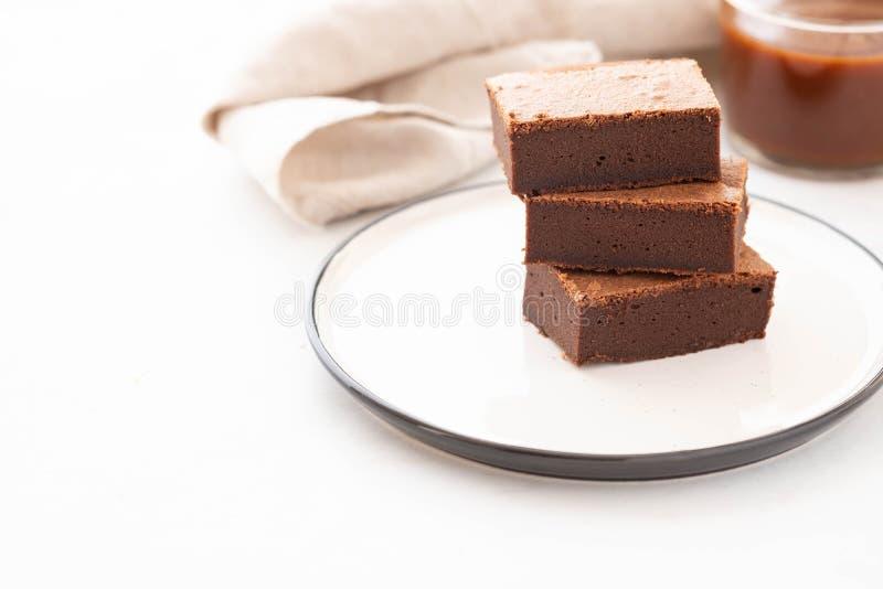 Il quadrato del brownie del cioccolato collega in pila sul piatto bianco Dessert delizioso tradizionale americano Copi lo spazio immagine stock libera da diritti
