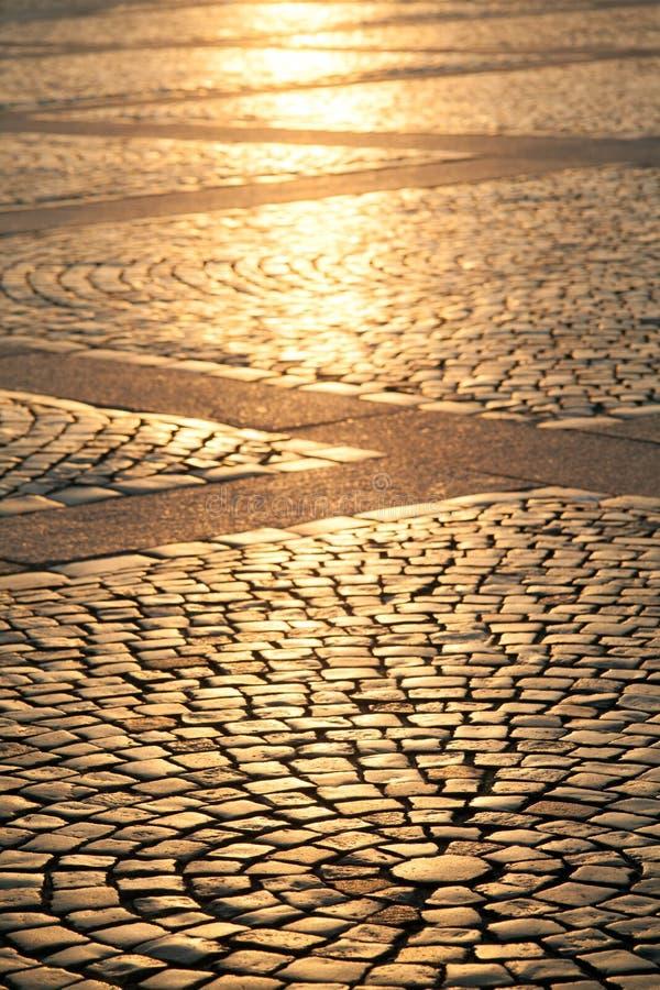 Il quadrato della pavimentazione di vecchia città nei raggi del ev di tramonto immagini stock