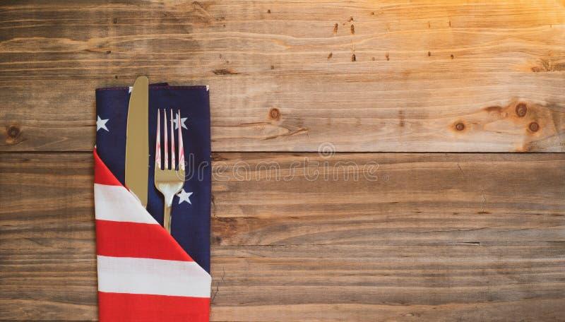Il quarto della Tabella di luglio dispone la regolazione con il tovagliolo della bandiera e dell'argenteria su fondo di legno rus fotografia stock