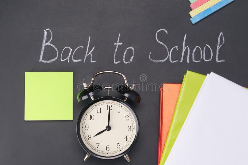 Il réveil montre au temps huit heures dans la perspective du panneau de craie et des matières d'enseignement, il est temps d'alle photographie stock libre de droits