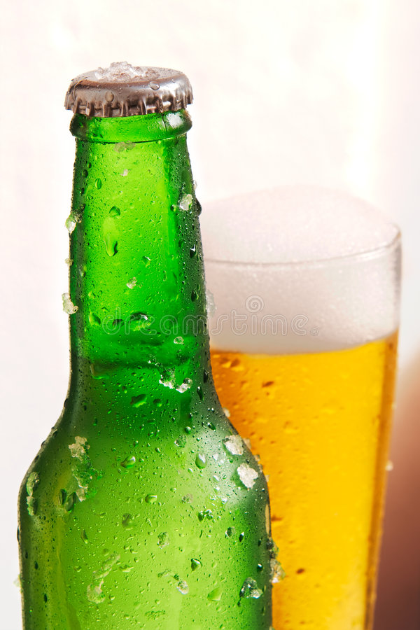 Il raccolto della bottiglia e del vetro di birra fotografia stock