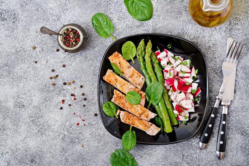 Il raccordo del pollo ha cucinato su una griglia con un contorno della salsa del ravanello e dell'asparago fotografia stock
