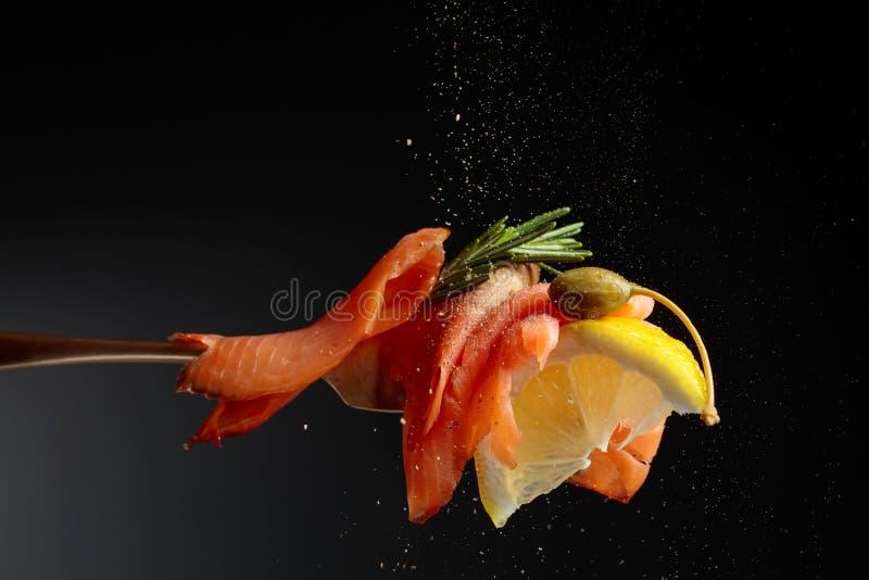 Il raccordo della trota, la fetta del limone, i capperi ed i rosmarini spruzzano con pepe fotografia stock