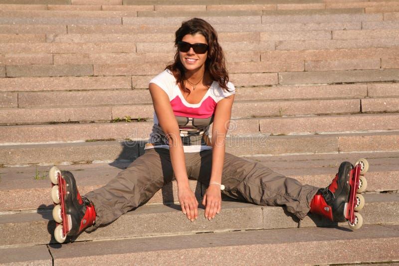 il Ragazza-rullo si siede sulle scale fotografia stock libera da diritti
