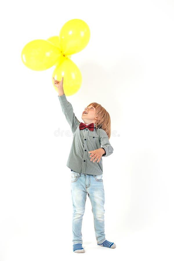 Il ragazzino alla moda si è vestito in aerostato rosso della tenuta del farfallino isolato su fondo bianco fotografia stock libera da diritti
