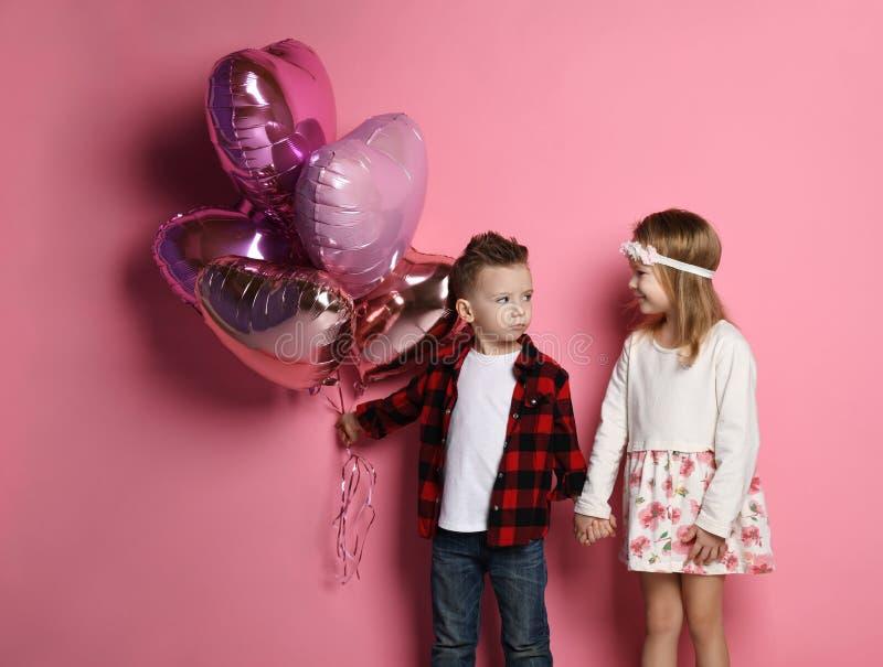 Il ragazzino avido non vuole dare alla ragazza gli impulsi del cuore, ma ancora si tengono per mano fotografia stock