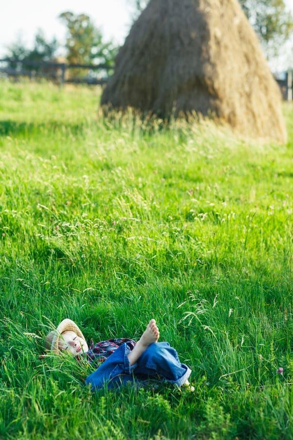 Il ragazzino bello si rilassa su erba fotografia stock libera da diritti