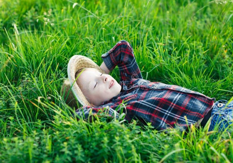 Il ragazzino bello si rilassa su erba immagini stock libere da diritti