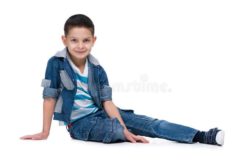 Il ragazzino bello si siede sui precedenti bianchi immagine stock libera da diritti