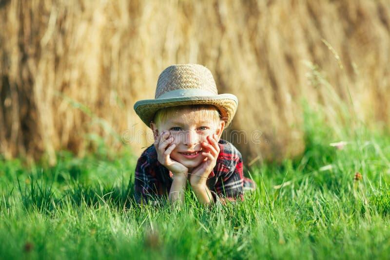 Il ragazzino bello si trova su erba su fondo del mucchio di fieno fotografie stock libere da diritti