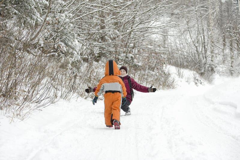 Il ragazzino in camici che passa la neve verso la madre Giorno di inverno nella vista posteriore della foresta di conifere immagini stock