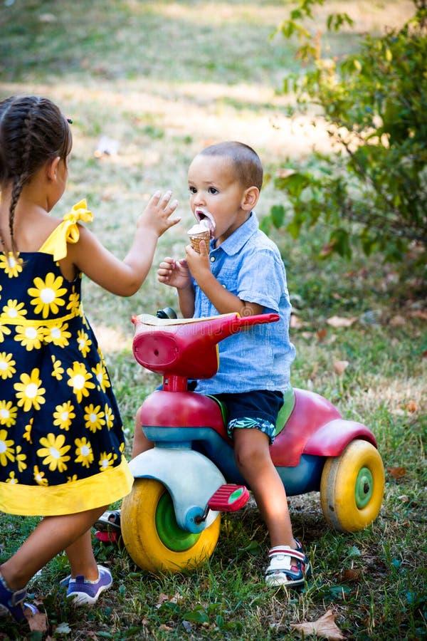 Il ragazzino che mangia il gelato si siede sul piccolo triciclo mentre il suo sist fotografia stock libera da diritti