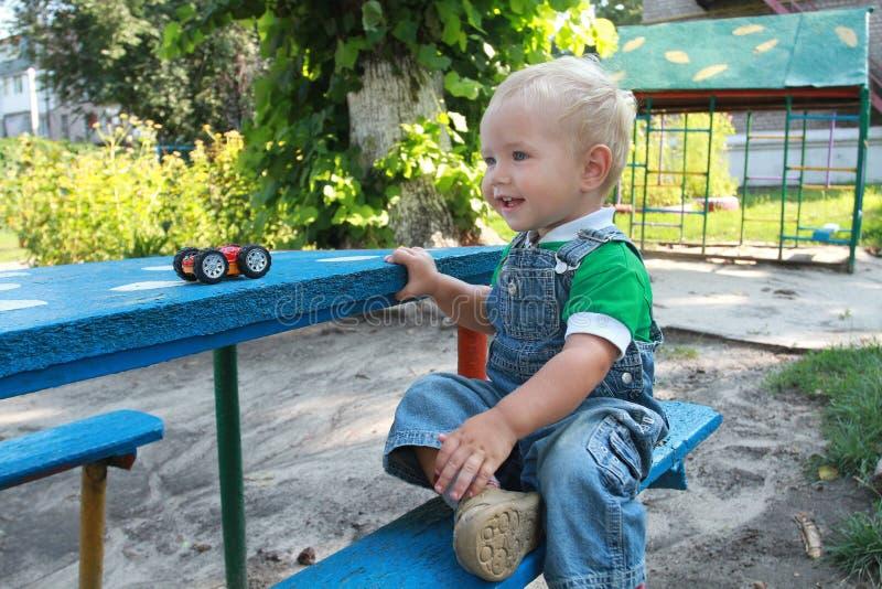 Il ragazzino che si siede ad una tavola nel parco immagini stock