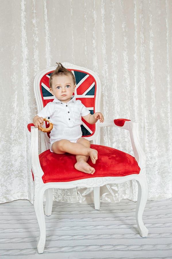 Il ragazzino che si siede in una sedia gradisce un reale immagine stock