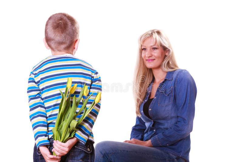 Il ragazzino con i fiori della tenuta della madre dietro appoggia fotografia stock libera da diritti