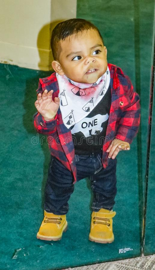 Il ragazzino con le stampe della bandana dello stainer della camicia e dell'alimento di plaid fiuta e dice per eliminare la fabbr fotografia stock libera da diritti
