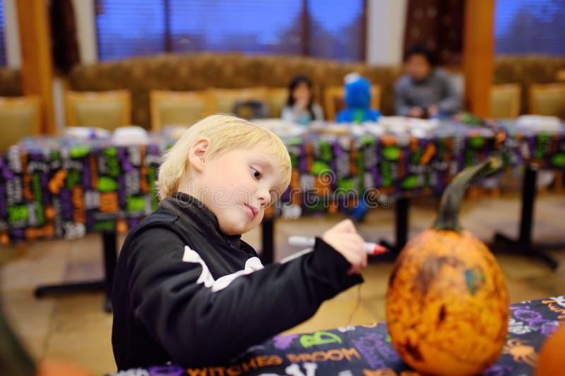Il ragazzino in costume di scheletro spaventoso dipinge la zucca sul partito di Halloween per i bambini fotografia stock libera da diritti