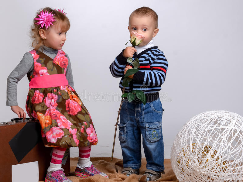 Il ragazzino dà ad una ragazza una rosa, isolata su bianco immagini stock libere da diritti