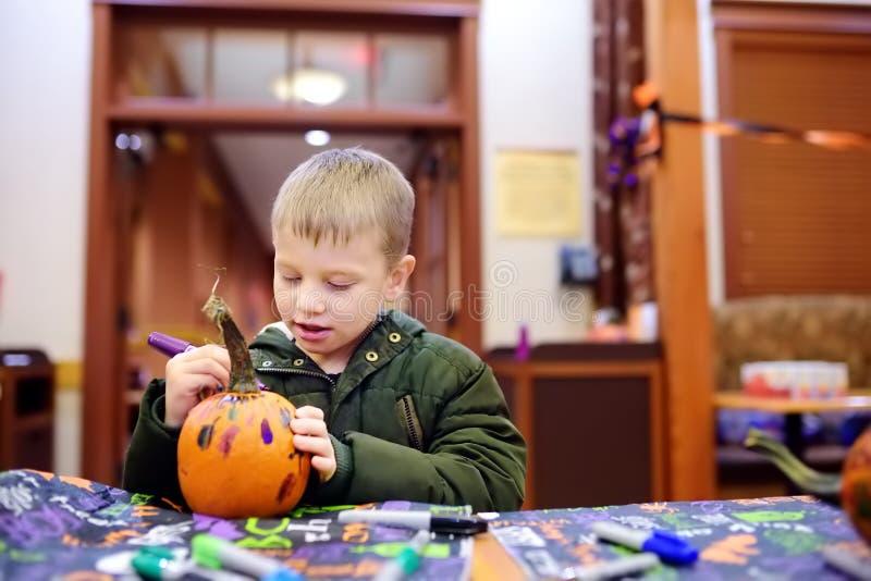 Il ragazzino dipinge la zucca sul partito di Halloween per i bambini immagine stock libera da diritti
