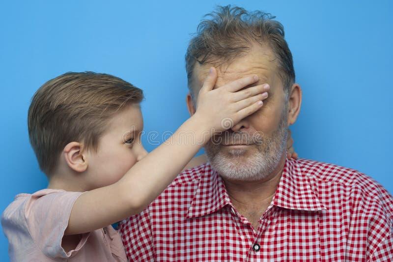Il ragazzino divertente chiude i suoi occhi al nonno immagine stock