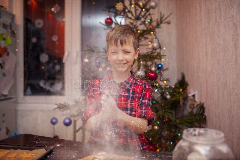 Il ragazzino divertente sta preparando il biscotto, cuoce i biscotti nella cucina di Natale immagini stock