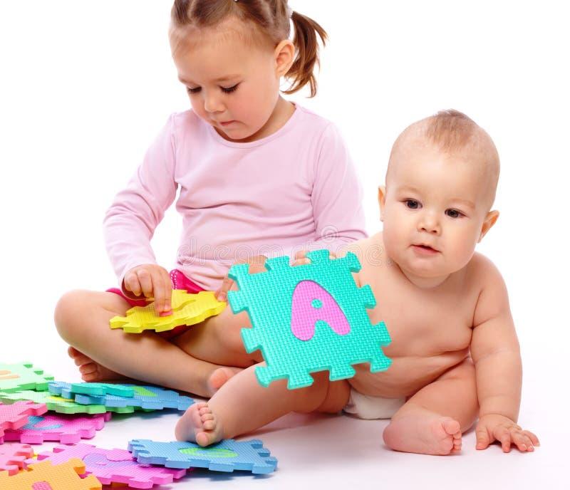 Il ragazzino e la ragazza stanno giocando con l'alfabeto fotografie stock