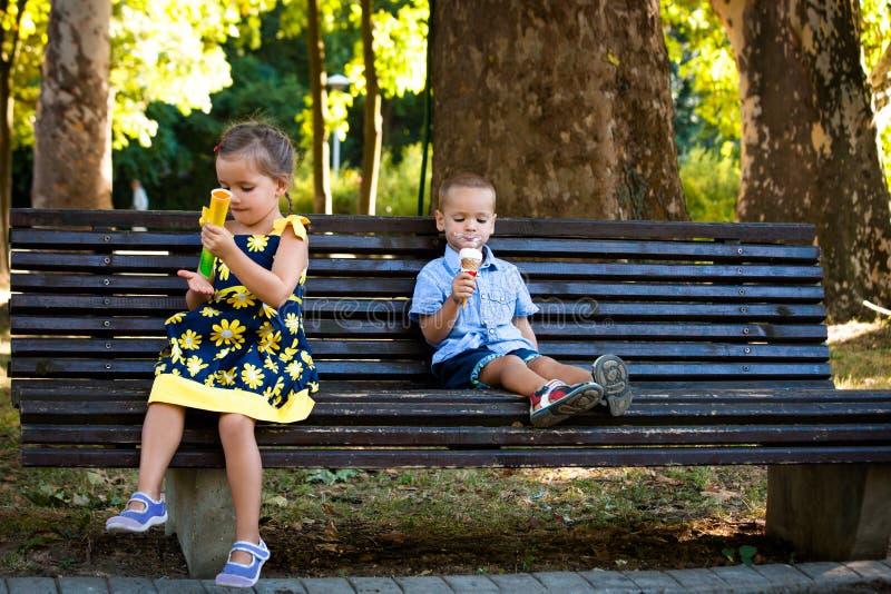 Il ragazzino ed il fratello e la sorella della ragazza che mangiano il gelato si siedono sulla b immagine stock