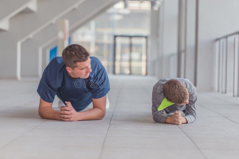 Il ragazzino ed suo padre che fare spinge aumenta gli esercizi fotografia stock libera da diritti