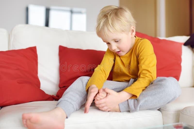 Il ragazzino esamina la gamba irritata che si siede sullo strato all'interno Trauma, contusione, scheggia fotografie stock libere da diritti