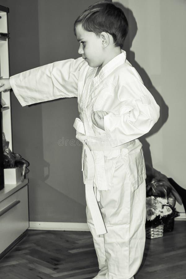 Il ragazzino fa gli esercizi di karatè immagine stock