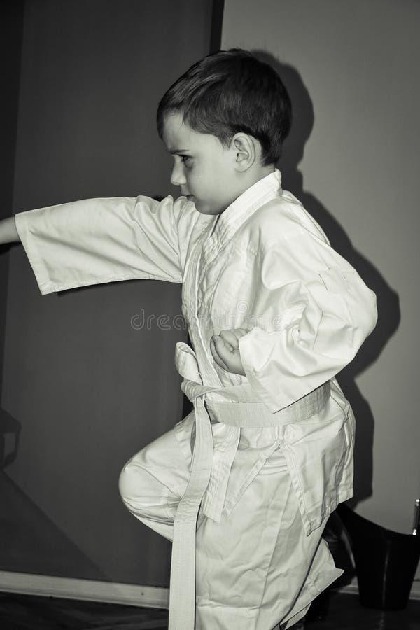 Il ragazzino fa gli esercizi di karatè fotografie stock