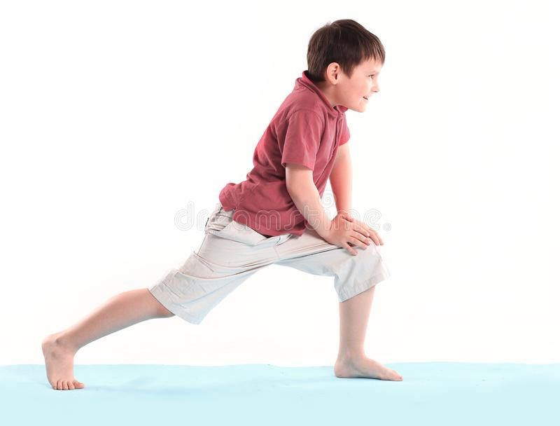 Il ragazzino fa gli esercizi di mattina Isolato su priorit? bassa bianca fotografia stock libera da diritti