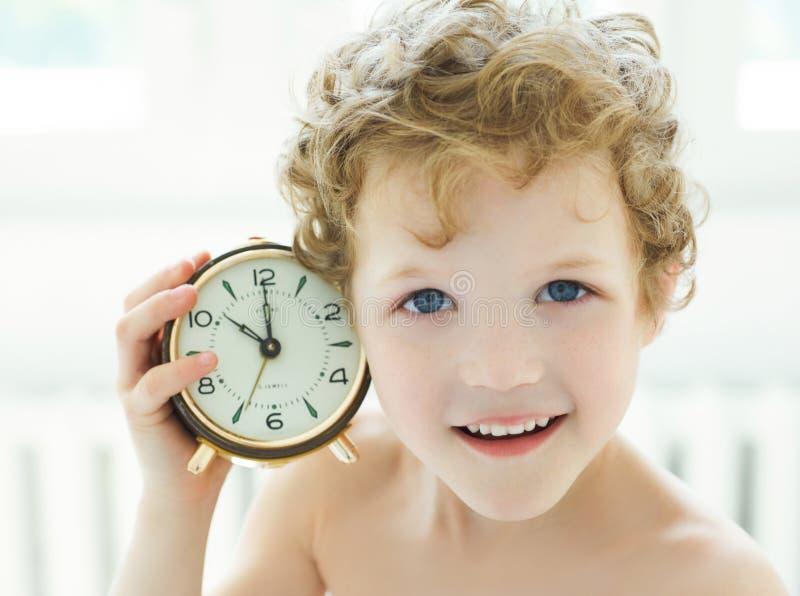 Il ragazzino felice ascolta un orologio antico Un giovane ragazzo riccio-dai capelli ha svegliato a letto nelle prime ore del mat immagini stock