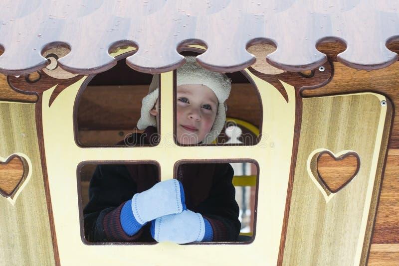Il ragazzino felice gioca sul campo da giuoco nell'inverno immagini stock libere da diritti
