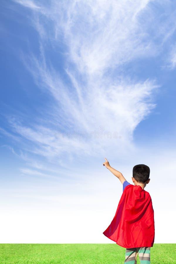 Il ragazzino felice ha indossato il vestito ed il punto del supereroe al cielo fotografia stock
