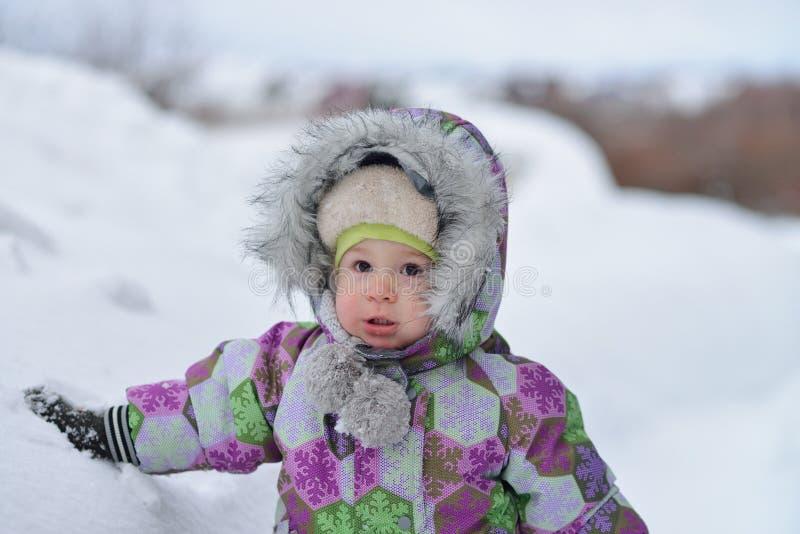 Il ragazzino felice sta giocando con neve sul fondo del winer immagini stock