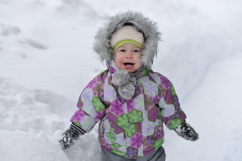 Il ragazzino felice sta giocando con neve sul fondo del winer immagini stock libere da diritti