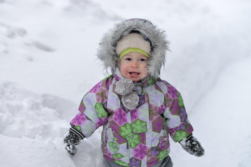 Il ragazzino felice sta giocando con neve sul fondo del winer fotografie stock libere da diritti