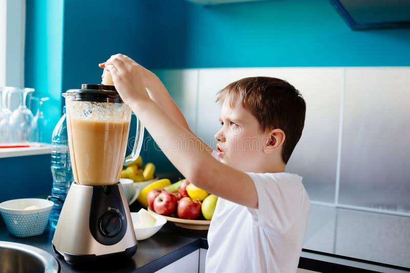 Il ragazzino felice sta producendo il succo di frutta sano a casa fotografie stock