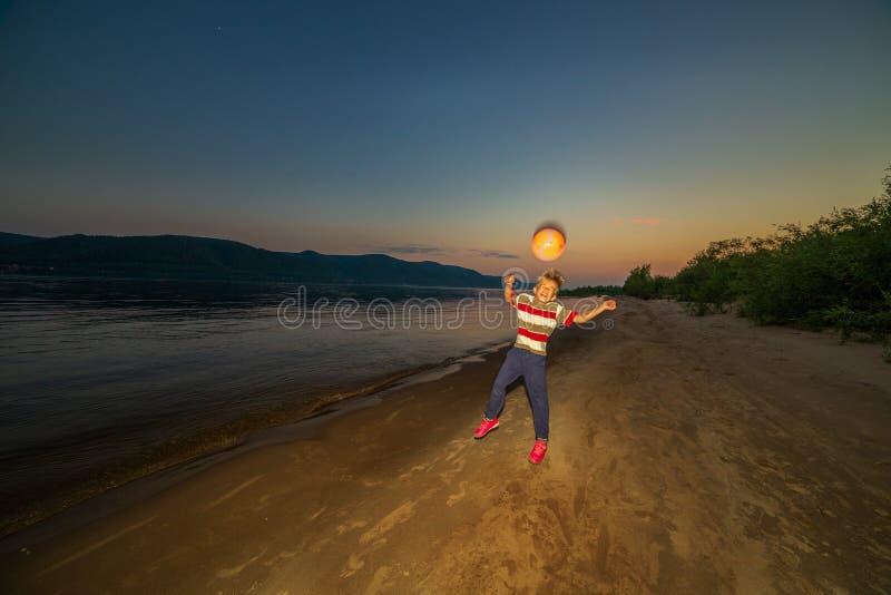 Il ragazzino gioca la palla sulla spiaggia immagini stock libere da diritti