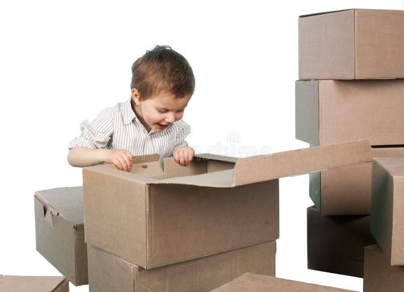 Il ragazzino guarda in una scatola fotografia stock