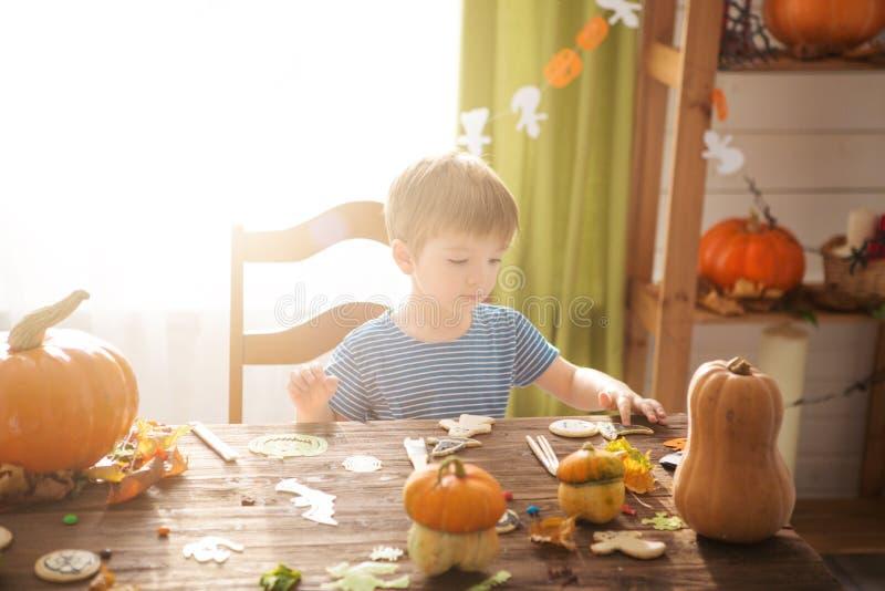 Il ragazzino ha decorato i biscotti per Halloween Ragazzo sveglio del bambino che prepara per una celebrazione di Halloween fotografie stock