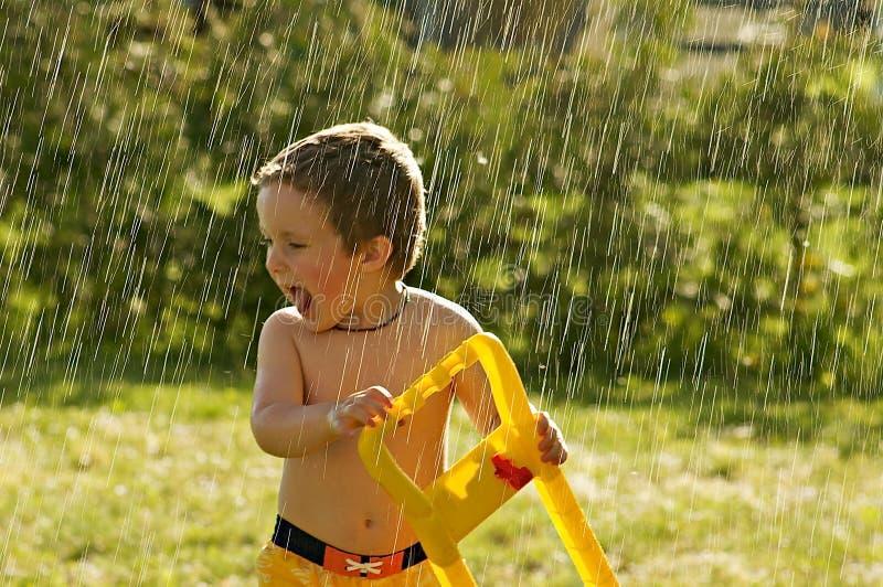 Giocando nella pioggia fotografia stock