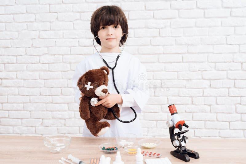 Il ragazzino impara la professione di un medico Il ragazzo moro vuole diventare un medico fotografia stock