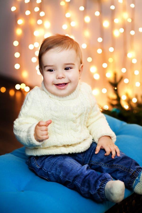 Il ragazzino in maglione bianco si siede nella pioggia delle luci e della risata fotografia stock