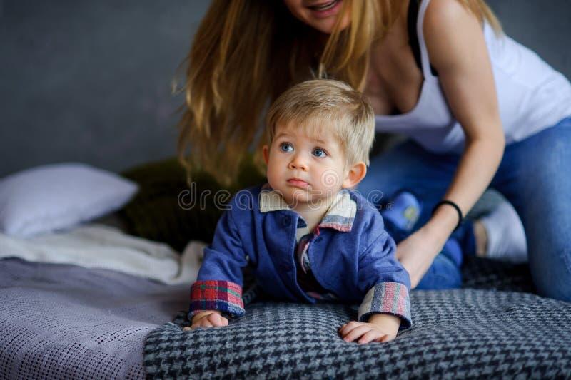 Il ragazzino in modo divertente si trova su un grande letto immagine stock