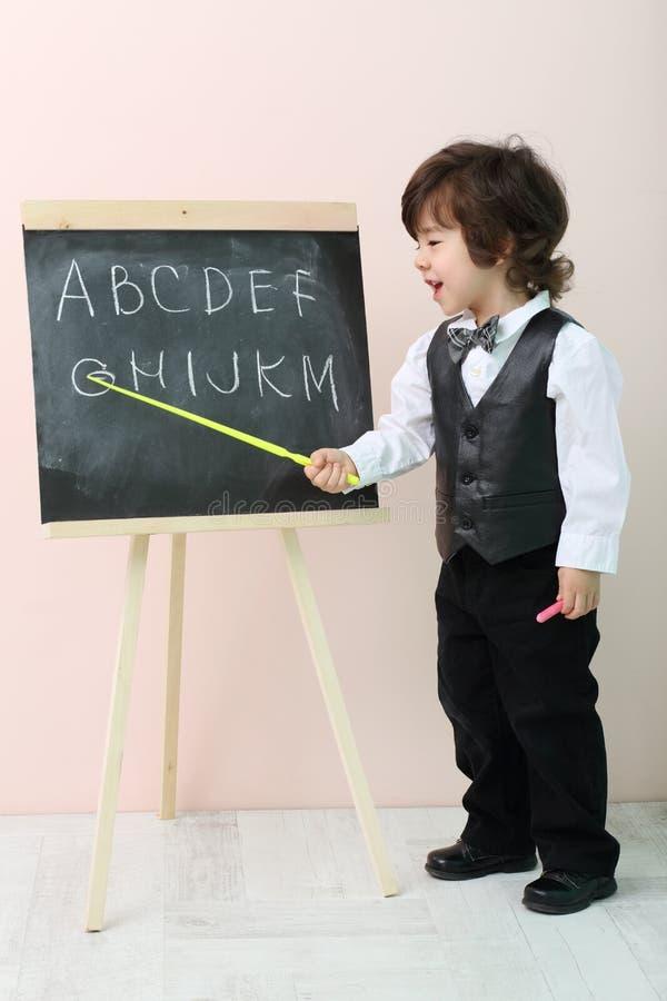Il ragazzino mostra dalle lettere gialle del puntatore alla lavagna fotografie stock