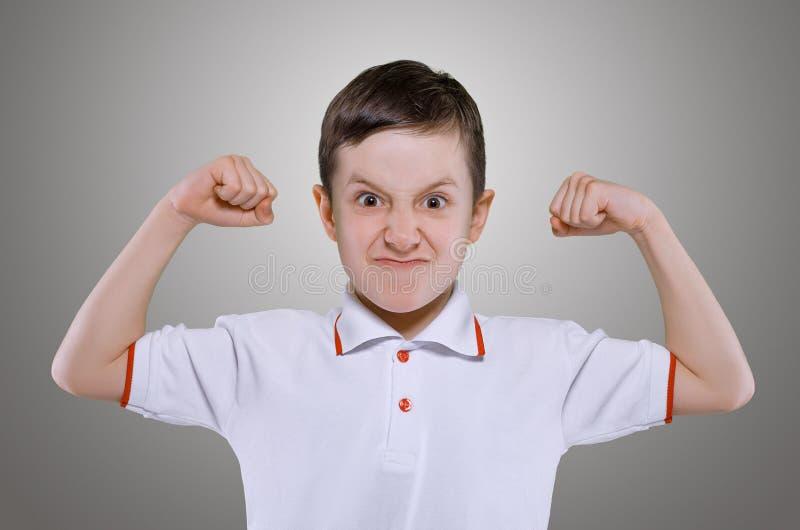Il ragazzino mostra la forza immagine stock