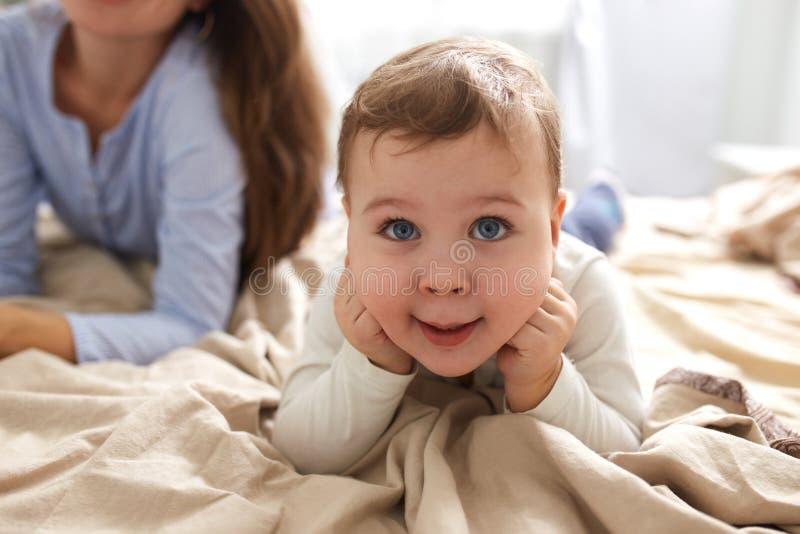 Il ragazzino pone con le sue mani sotto il suo mento sul letto con la coperta beige nella camera da letto immagini stock libere da diritti